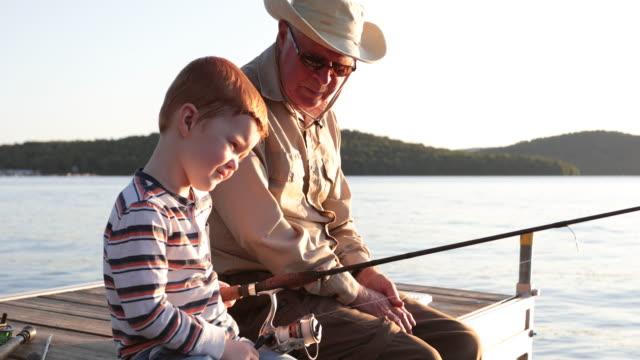 vídeos de stock, filmes e b-roll de pesca do avô e do neto no por do sol no verão - avô
