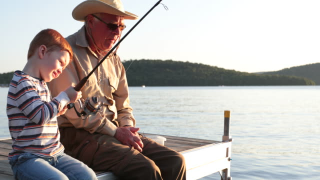 grandfather and grandson fishing at sunset in summer - fisher role stock videos & royalty-free footage