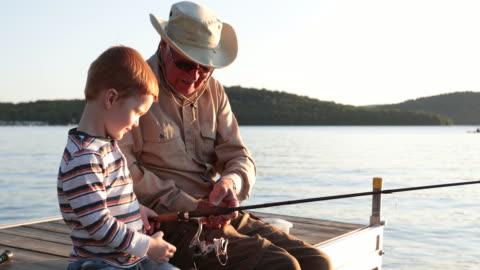 vídeos de stock, filmes e b-roll de pesca do avô e do neto no por do sol no verão - pescaria