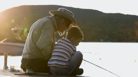 grandfather and grandson fishing at sunset in summer - grandson stock videos & royalty-free footage