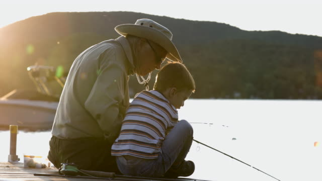 grandfather and grandson fishing at sunset in summer - active seniors stock videos & royalty-free footage