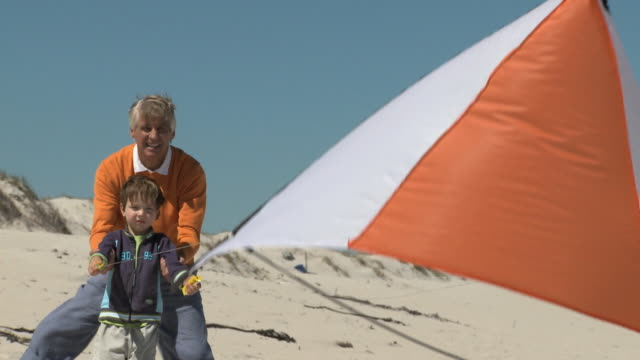 ws pan grandfather and grandson (4-5) flying kite / cape town, south africa - kite toy stock videos and b-roll footage