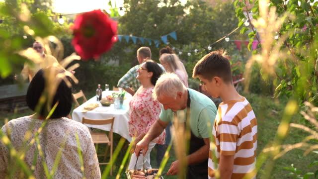 stockvideo's en b-roll-footage met grootvader en kleinzoon die vlees samen tijdens partij bij binnenplaats grillen - jong van hart