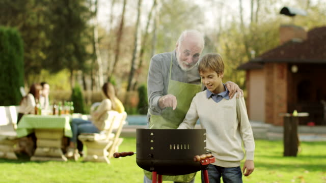 grandfather and grandson having a barbecue - barbecue grill stock videos and b-roll footage