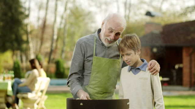 grandfather and grandson having a barbecue - male animal stock videos & royalty-free footage
