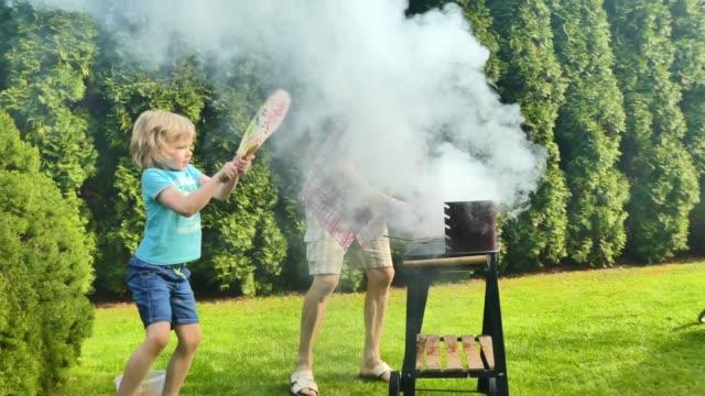 vidéos et rushes de grand-père et son petit-fils ayant un barbecue. - barbecue jardin