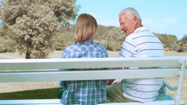 vídeos y material grabado en eventos de stock de ds abuelo y nieto teniendo una conversación en banco del parque - camisa de polo
