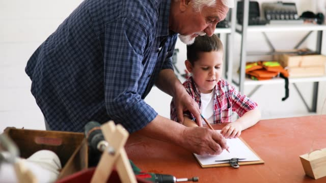 grandfather and grandson in workshop - diy stock videos & royalty-free footage