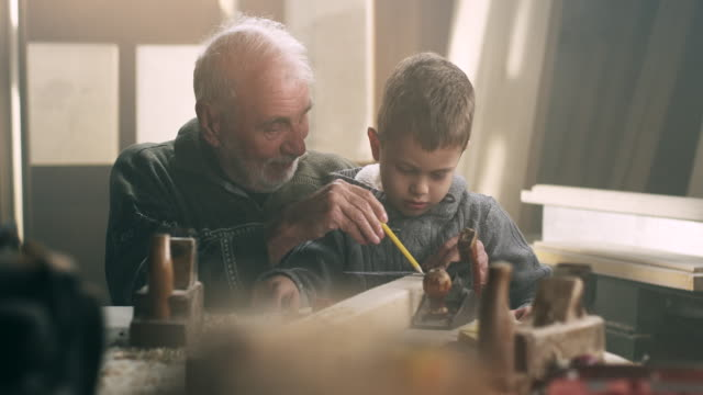 grandfather and grandson in workshop - multi generation family stock videos & royalty-free footage