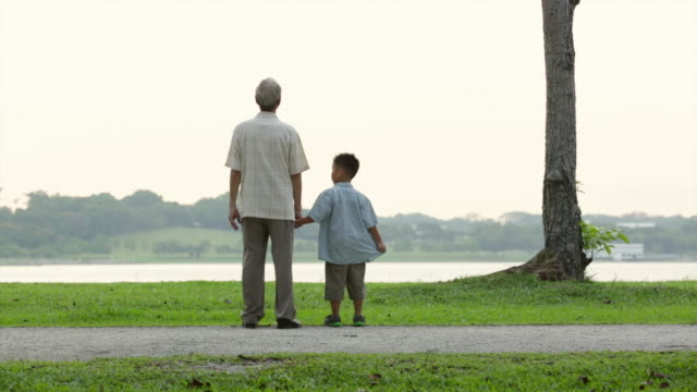 WS Grandfather and grandson looking at lake holding hands