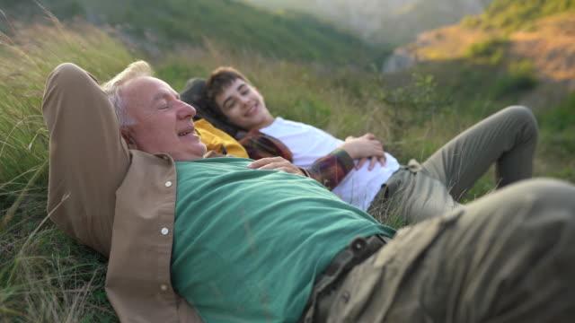 vídeos y material grabado en eventos de stock de abuelo y nieto tumbado en la hierba y disfrutando juntos del tiempo durante el senderismo - 65 69 años