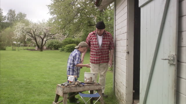 Grandfather and grandson painting their summer cottage Sweden.