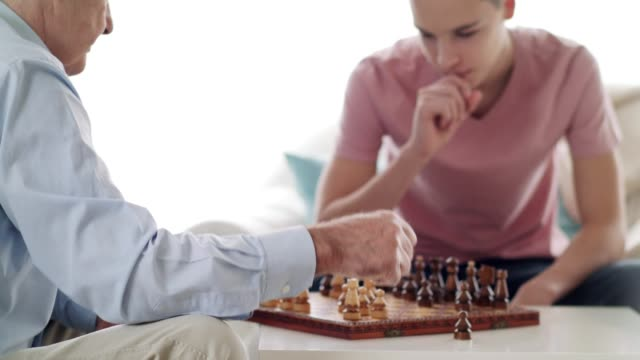grandfather and grandson playing chess at home - chess stock videos & royalty-free footage