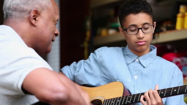 vídeos y material grabado en eventos de stock de cu pan grandfather and grandson playing guitar together in garage / richmond, virginia, united states - rock moderno