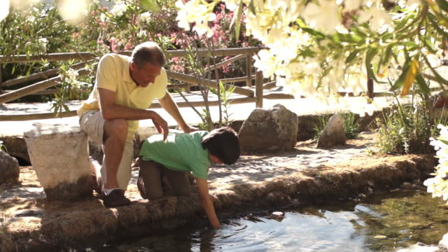 grandfather and grandson playing in water in park. - 祖父点の映像素材/bロール