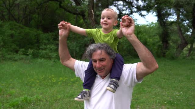 vídeos de stock, filmes e b-roll de avô e neto brincando juntos - homens maduros