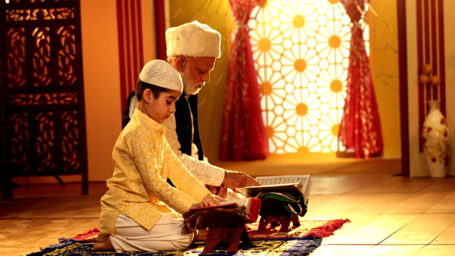 ms grandfather and grandson reading quran at home / delhi, india - religious celebration stock videos and b-roll footage