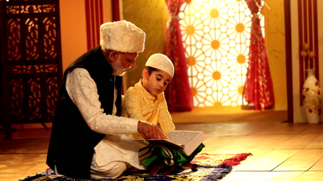 ms zi grandfather and grandson reading quran at home / delhi, india - religion stock-videos und b-roll-filmmaterial