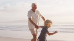 Grandfather And Grandson Running Along Beach In Slow Motion