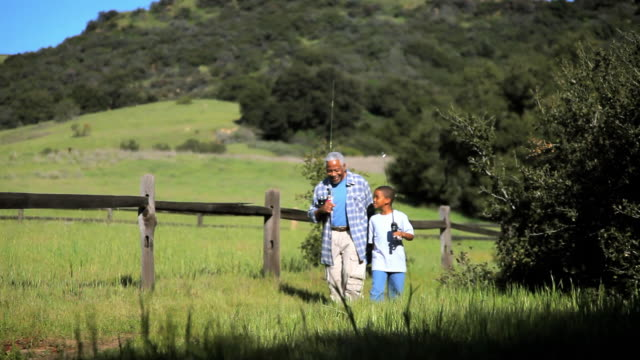 WS TS MS Grandfather and grandson (8-9) walking down through grassy fields with fishing poles on their shoulders / Los Angeles, California, USA
