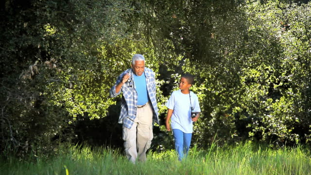 WS MS Grandfather and grandson (8-9) walking down trail with fishing poles on their shoulders / Los Angeles, California, USA