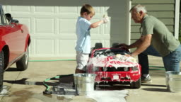 Grandfather and Grandson wash toy car together