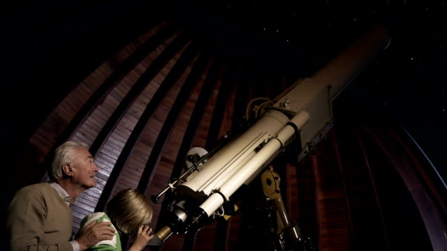 Grandfather and grandson with telescope