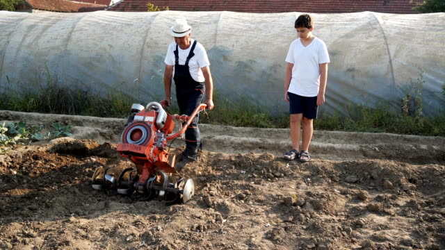 grandfather and grandson working on a mower - harrow stock videos & royalty-free footage
