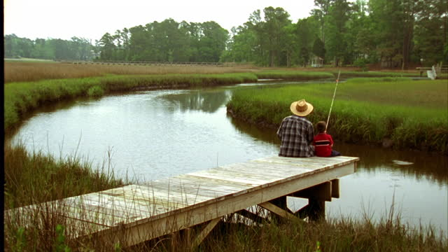 A grandfather and his grandson sit on a dock and fish in a river.