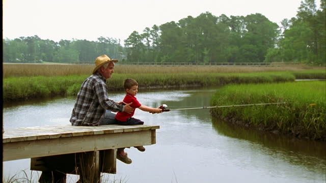 a grandfather and his grandson sit on a dock and fish in a river. - wilmington north carolina stock-videos und b-roll-filmmaterial