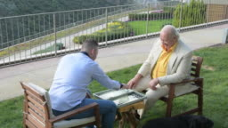 Grandfather and his son are playing backgammon in the garden
