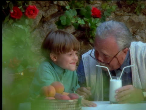 Grandfather + boy drinking from glass of milk with 2 straws outdoors