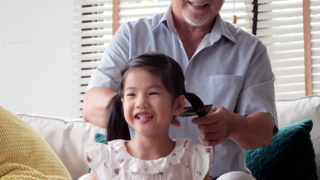grandfather brushing off granddaughter hair.charming little girl is smiling while his grandfather is combing granddaughter hair.happy family.families in hong kong - combing stock videos & royalty-free footage