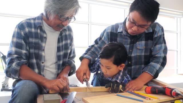 großvater zimmermann lehren enkelkind arbeiten und sprechen in der werkstatt - three people stock-videos und b-roll-filmmaterial