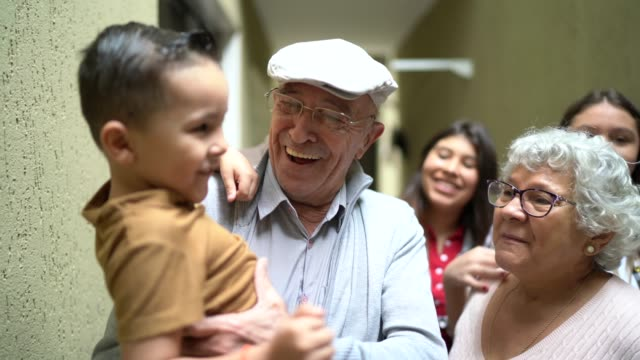 grandfather carrying grandson during a family reunion - reunion social gathering stock videos & royalty-free footage
