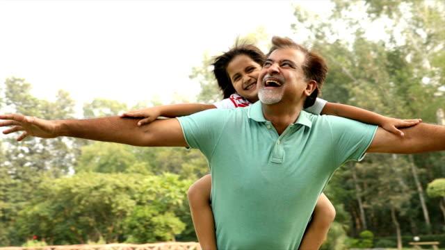 ms pan grandfather carrying grandson on his back / delhi, india - おんぶ点の映像素材/bロール