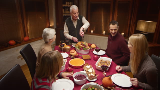 grandfather carving the thanksgiving turkey - thanksgiving plate stock videos & royalty-free footage