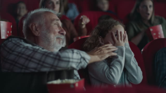 grandfather consoling scared girl in cinema - film industry stock videos & royalty-free footage