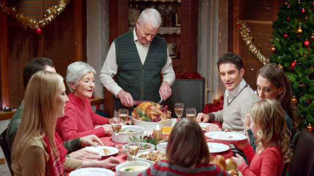 stockvideo's en b-roll-footage met grandfather cutting and passing on the christmas turkey - koken eten koken