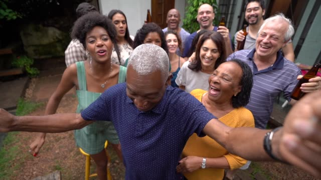 grandfather dancing with friends/family at barbecue party - large family stock videos & royalty-free footage