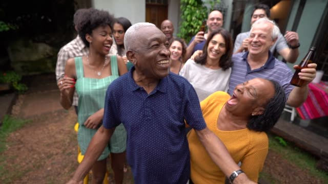 grandfather dancing with friends/family at barbecue party - social gathering stock videos & royalty-free footage
