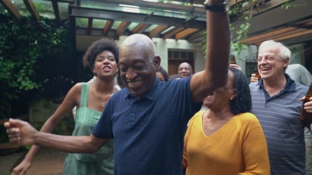 grandfather dancing with friends/family at barbecue party - retirement stock videos & royalty-free footage
