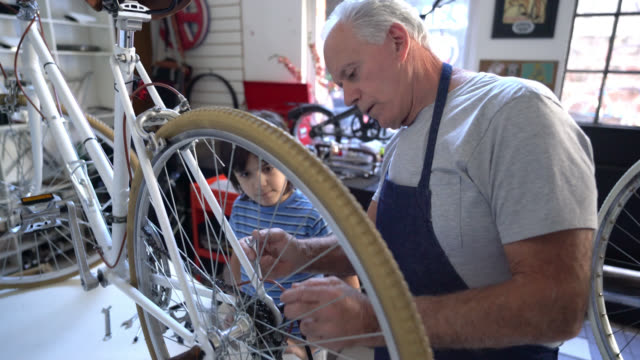 grandfather doing maintenance to a bicycle at the shop and grandson paying close attention - aggiustare video stock e b–roll