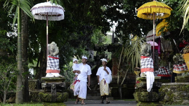ms td grandfather, father and son in traditional clothes coming out of colorful decorated pura dalem puri temple / ubud, bali, indonesia - ubud district stock videos & royalty-free footage