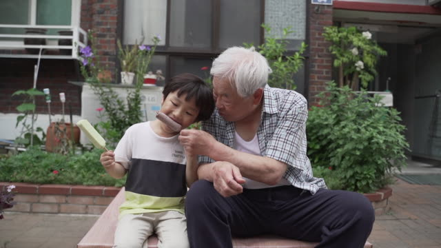 grandfather feeding ice cream to his grandson, sitting in front of the house, seoul, south korea - vest stock videos & royalty-free footage