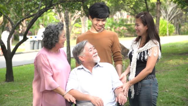 großvater fühle mich glücklich mit seinem lächeln durch familie gruß im park - großeltern stock-videos und b-roll-filmmaterial