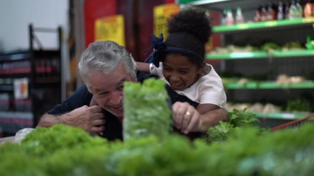 grandfather having fun choosing some lettuce with granddaughter at supermarket - alternative energy stock videos & royalty-free footage