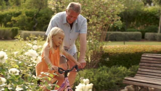 vidéos et rushes de grandfather helping granddaughter learn to ride a bike in park. - petite fille