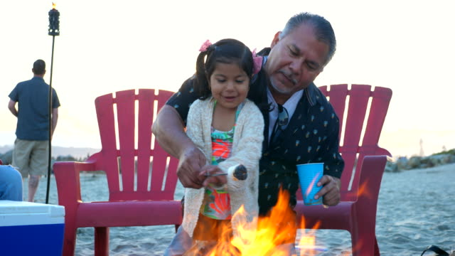 ms grandfather helping granddaughter roast marshmallow over fire during beach party with family - latin american and hispanic ethnicity stock videos & royalty-free footage