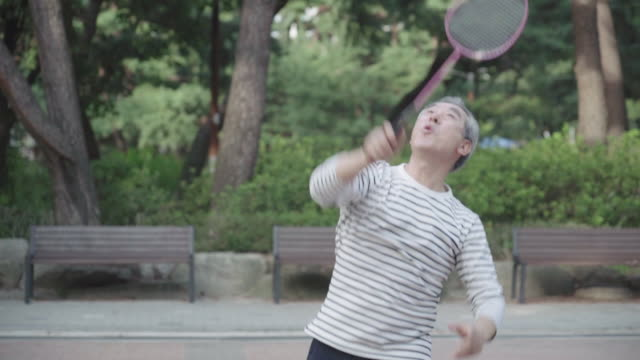 vidéos et rushes de a grandfather hits a shuttlecock at park - badminton sport